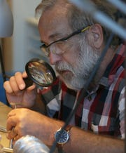 Jim Gordon uses a magnifying glass to take a closer look at a stone that he is cutting and polishing in the Jewelry & Fine Metals Studio at BARN (Bainbridge Artisan Resource Network) on Monday. Gordon is also building a wooden sailboat in the Woodworking Studio of BARN.