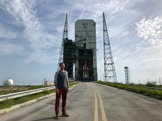 Spacecraft integrator Connor Murphy stands in front of the the Delta IV medium getting ready for its final launch from Launch Complex 37 at Cape Canaveral Air Force Station