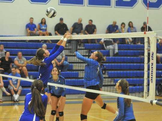 Wynford's Lainey Holman tips the ball over Crestline's Kennedy Moore at the net.