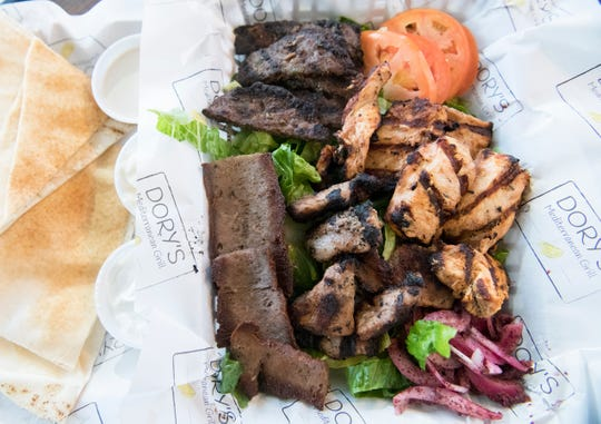 A protein combination platter featuring gyro, kafta, pork souvlaki, chicken taouk, pita, and sauces is displayed at Dory's Mediterranean Grill in Medford.