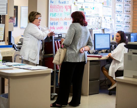 Scarlet Hudson talks with nurses at St. Elizabeth-Fort Thomas' IV and antibiotics floor, where Hudson offers pastoral care to patients and advice to those caring for the addicted.