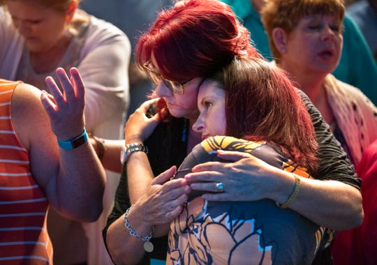 Scarlet Hudson prays with Kelly at the end of a service at Church on Fire in Harrison.