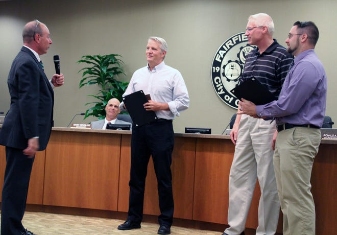 Fairfield Mayor Steve Miller, left, gave proclamations to Greg Uhler and Joshua Higgins, far right, after they assisted Charlie Fisher after he suffered a heart attack returning home from a bike ride.