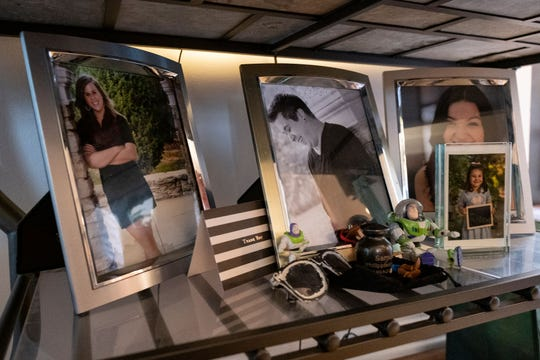 Samuel Gillman's photo and a tiny urn stand among family photos in his mother Katie Renfrow's Westwood home. Samuel died of an overdose in 2017.