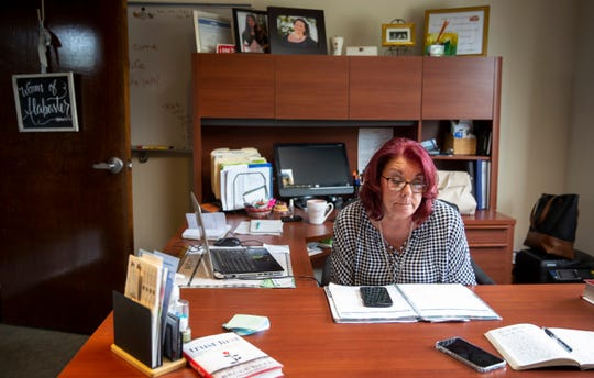 Scarlet talks on her phone while at her office in her nonprofit Women of Alabaster, a faith-based ministry for victims of human trafficking and addiction.