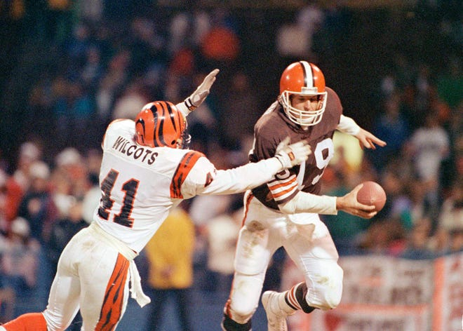 Cleveland Browns quarterback Bernie Kosar (19) is chased from the pocket by Cincinnati Bengals cornerback Solomon Wilcots (41) late in their 34-13 loss to the Bengals in Cleveland, Oct. 23, 1990. Kosar eluded Wilcots but was eventually sacked by Jason Buck. (AP Photo)