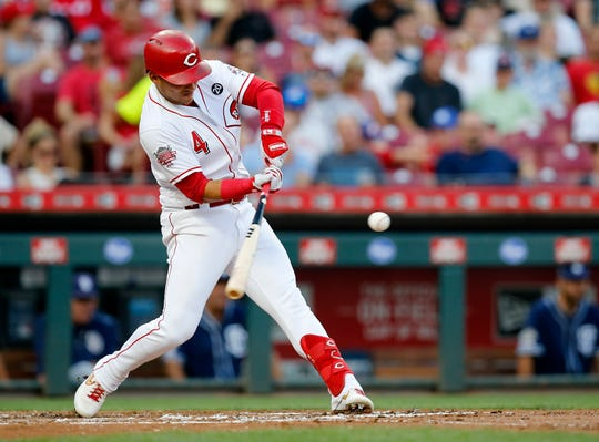 Cincinnati Reds shortstop Jose Iglesias (4) hits a single in the first inning of the MLB National League game between the Cincinnati Reds and the San Diego Padres at Great American Ball Park in downtown Cincinnati on Monday, Aug. 19, 2019.