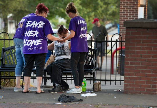 Scarlet Hudson prays with a woman sitting on a bench in East Price Hill. Twice monthly, Scarlet and a team of volunteers do outreach, offering food, prayer an talk time.