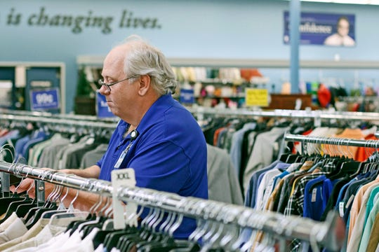 John organizes clothing at a Goodwill store in Clarksville