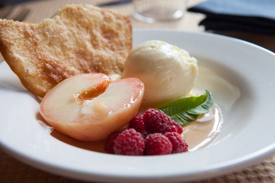 Poached white peaches in a peach simple syrup with vanilla ice cream and raspberries at Canal House Station in Milford.
