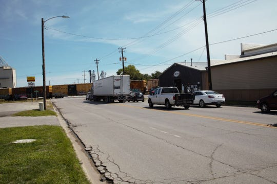 Cars on Hubbell Avenue in Des Moines wait for a train to pass for about 15 minutes on Tuesday. The day before, a train had blocked the street for more than an hour.