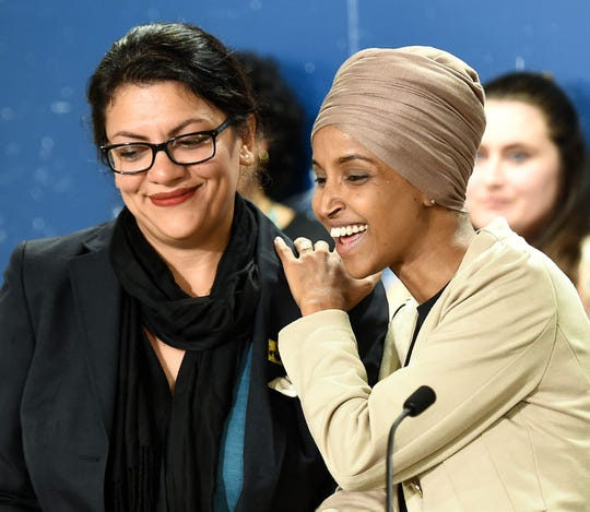 Representative from Minnesota Ilhan Omar, right, and Democratic Representative from Michigan Rashida Tlaib, left, laugh during a news conference at the Minnesota state capitol in St. Paul, Minnesota on Aug. 19, 2019.