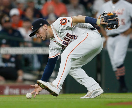 Alex Bregman makes an attempt on a bunt by a Tigers hitter in the first inning Monday in Houston.