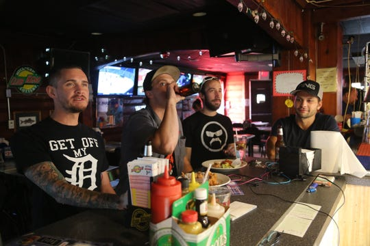 From left: Neil Johns, 31, of Wyandotte; Mitch Keehn, 24, of Wyandotte; Josh Charles, 28, of Wyandotte; and David Thomas, 28, of Grand Rapids, enjoy drinks and a snack at Frank's Cafe in Wyandotte.