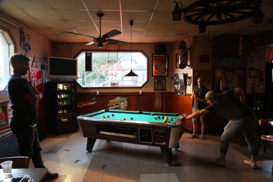 Guys play pool at the Chene Adele bar in Wyandotte on Aug. 2, 2019, the day before the bar closed for good after being purchased by the city.