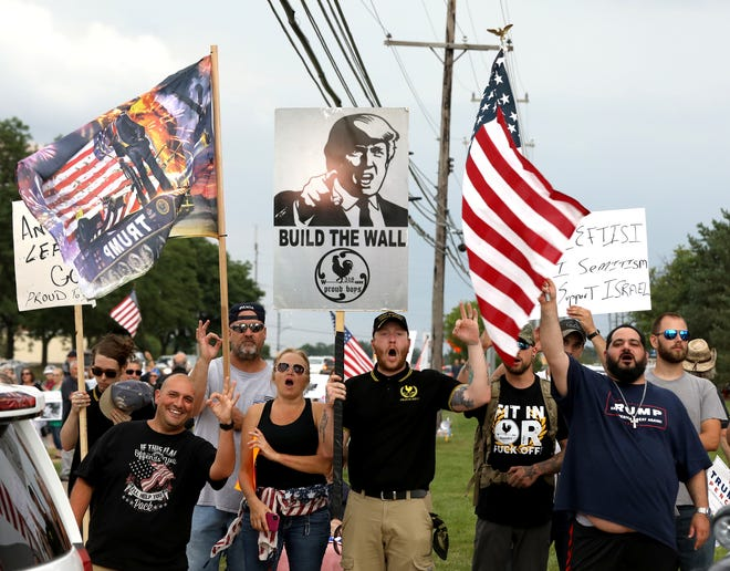 """In this file photo from August of 2019, members of the Proud Boys hold up the white power sign when yelling towards people protesting the detention of migrants at the U.S. southern border. The Proud Boys joined others in a counter-protest about immigration and use of the word """"camps"""" or """"concentration camps"""" when talking about the detentions in competing rallies held in front of the Holocaust Memorial Center in Farmington Hills, Michigan. A chapter of Proud Boys based in North Carolina and the conspiracy group QAnon are among groups expected to participate in a march on Saturday In Fayetteville that protests child sexual abuse and trafficking."""