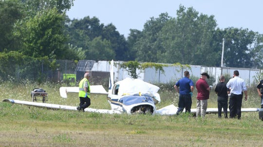 Investigators survey the scene of a plane crash Tuesday near the Livingston County airport.