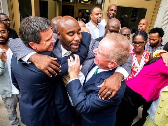 Mateen Cleaves, a Flint native known for his roles as a Michigan State and NBA basketball player, smiles as he embraces his attorneys Michael, left, and Frank J. Manley as he celebrates receiving a not guilty verdict on all counts from the jury as he steps outside of the Genesee County Circuit Court on Tuesday.