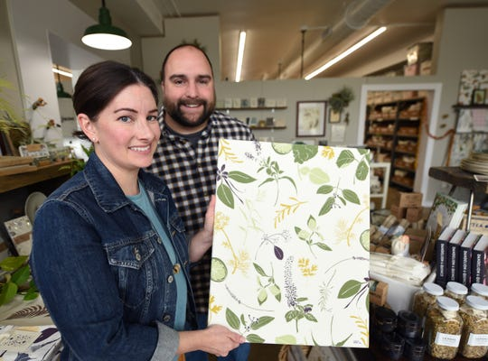Owners Katie and her husband Nick Forte holds a stretch canvas.