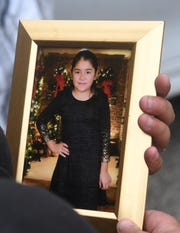 Claudia Stapleton holds a portrait of her 9-year-old niece Emma Hernandez.