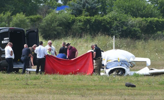 The Livingston County Medical Examiner's office works with first responders at the scene of a small airplane crash that killed two people Tuesday.  The single engine Rockwell Commander M200 plane crashed after takeoff at Livingston County's Spencer J. Hardy Airport, northwest of Howell.