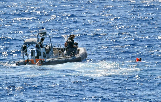 Italian Finance Police rescue a migrant who jumped off the Spanish humanitarian rescue ship Open Arms in a desperate bid to reach the shore of the Sicilian island of Lampedusa, southern Italy, tantalizingly near after 19 days blocked on board in deteriorating conditions by Italy's refusal to open its ports, Monday, Aug. 19, 2019.