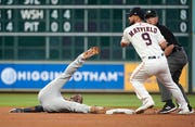 Detroit Tigers' Travis Demeritte, left, is tagged out by Houston Astros second baseman Jack Mayfield while trying to stretch a single into a double during the first inning.