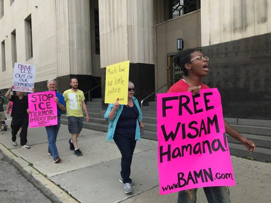 "Shawn Vaughn holds a sign reading ""Free Wisam Hamana"" outside the federal courthouse on Lafayette on Tuesday."
