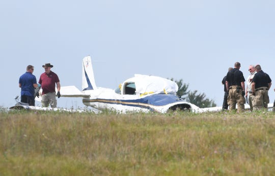 Investigators work the scene of a crash of a single engine Rockwell Commander M200 small airplane at Livingston County's Spencer J. Hardy Airport, northwest of Howell, Michigan on August 20, 2019.