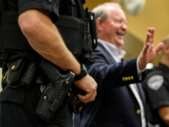 Flanked by two armed Evansville Police Department officers, U.S. Rep. Larry Bucshon, back, meets his constituents following a town hall meeting, in which he answered questions for about an hour and a half, at the Southern Indiana Career & Technical Center in Evansville, Ind., Monday evening, Aug. 19, 2019. He cited security concerns and expenses as a reason for not holding town halls more often.