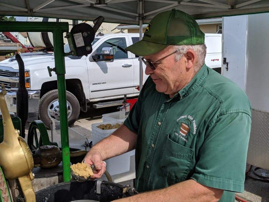 Carl Rader of Rader's Old Fashioned Ice Cream scoops out peanut butter ice cream from his churn, powered by a John Deere three-horse hit and miss engine.
