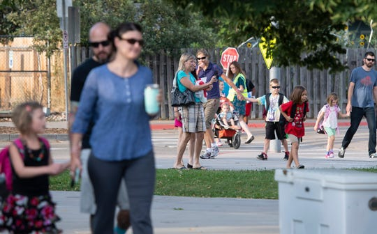 Parents walk with their kids outside Laurel Elementary School in Fort Collins on the first day of classes on Tuesday, Aug. 20, 2019.