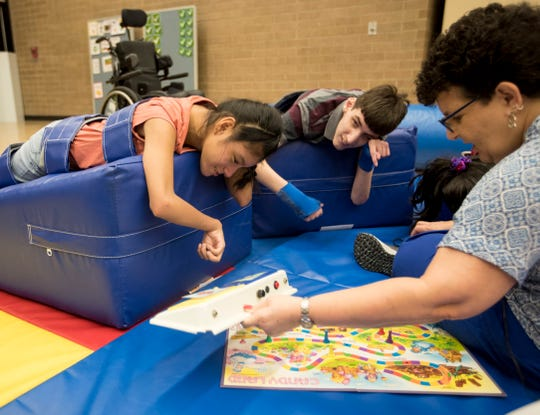 Gabriela Perez-Velazquez and Steven Neale, right, play a game with speech therapist Suzan Coger at the Buckingham Exceptional Student Center on Tuesday, August 20, 2019.