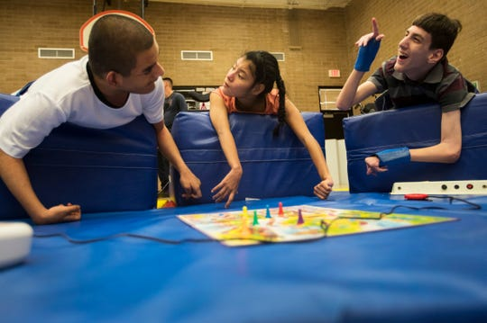 Saul Quintino-Nunez, left, Gabriela Perez-Velazquez and Steven Neale, right, interact while lying on the new wedge mats at the Buckingham Exceptional Student Center on Tuesday, August 20, 2019. The wedges, which are used for physical and occupational therapy, were bought with money raised by the Fort Myers Shores Fire Department and the Rotary Club of Fort Myers East.
