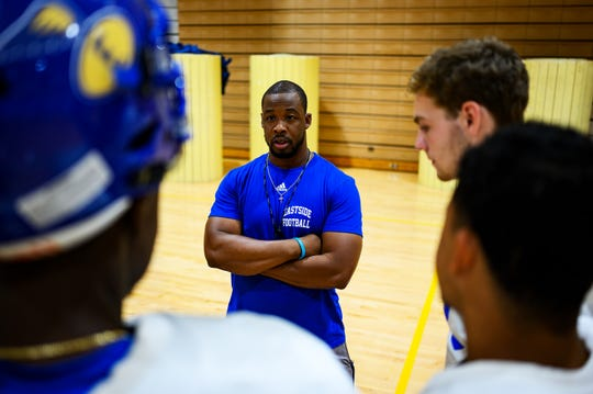 Eastside football coach Andre Woolcock speaks with some of his players practice drills Tuesday, Aug. 20, 2019.