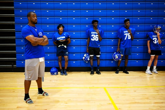 Eastside football coach Andre Woolcock observes his players practice drills Tuesday, Aug. 20, 2019.