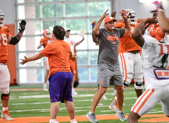 Clemson Head Coach Dabo Swinney leads jumping jacks with the team during practice at the Poe Indoor Facility at Clemson Tuesday, August 20, 2019.