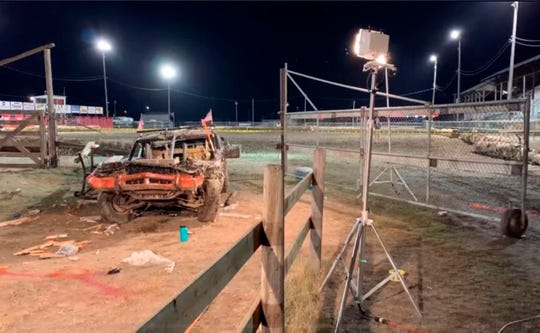 This Sunday, Aug. 18, 2019, image provided by ABC Fox Montana, shows the scene where a woman died after a car flew through a fence into spectators at a demolition derby in Deer Lodge, Montana. The Montana Standard reports at least eight people were sent to the hospital Sunday after a driver lost control of the car. Authorities say a woman in her 40s died at the hospital after being transported from Powell County Fairgrounds in Deer Lodge about 80 miles (130 kilometers) southeast of Missoula. (Brooke McCarthy/ABC Fox Montana via AP)