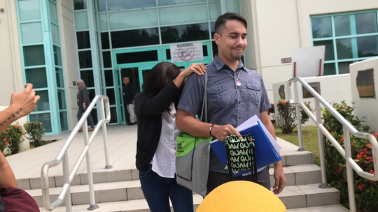 Jennifer Topacio, a GovGuam employee guilty of official misconduct in food stamp fraud case, hides from cameras behind Derick Evan Hills as they walk to the probation office on Tuesday, Aug. 20, 2019.