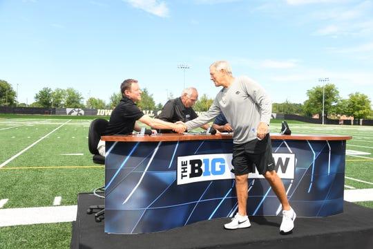Iowa head coach Kirk Ferentz greets BTN studio host Dave Revsine, left, following Tuesday's practice in Iowa City.