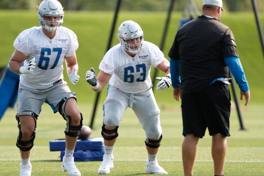 Lions offensive tackle Matt Nelson (67) and offensive guard Beau Benzschawel (63) perform a drill during training camp at the Detroit Lions Training Facility.