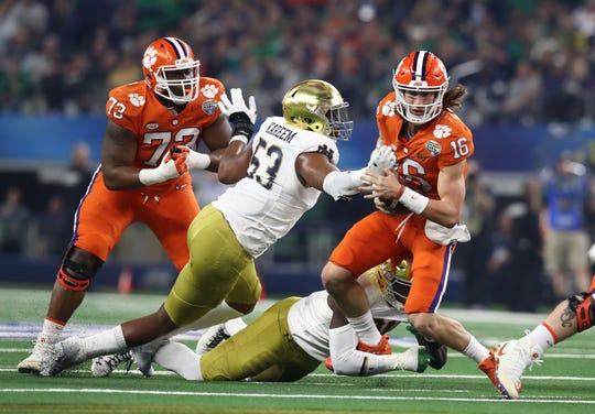 Clemson Tigers quarterback Trevor Lawrence (16) tries to run away from Notre Dame Fighting Irish defensive lineman Khalid Kareem (53)  in the first half in the 2018 Cotton Bowl college football playoff semifinal game at AT&T Stadium.