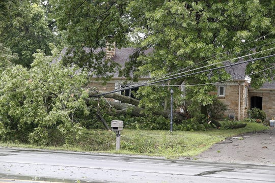 A strong afternoon thunderstorm knocked down trees and power lines in front of a home at 4400 S. Meridian St. on Tuesday, Aug. 20, 2019.