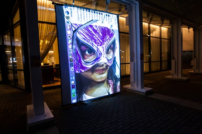 Miriam Alarcón Avila, of Tiffin, projects photos she took of children wearing custom lucha masks over a 3D sculpture, Monday, Aug. 19, 2019, at the Weatherdance fountain stage in the Pedestrian Mall in downtown Iowa City.