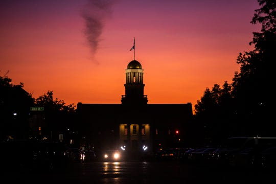 An orange and pink sky is illuminated as the sun sets behind the Old Capitol building, Monday, Aug. 19, 2019, on the University of Iowa campus in Iowa City, Iowa.
