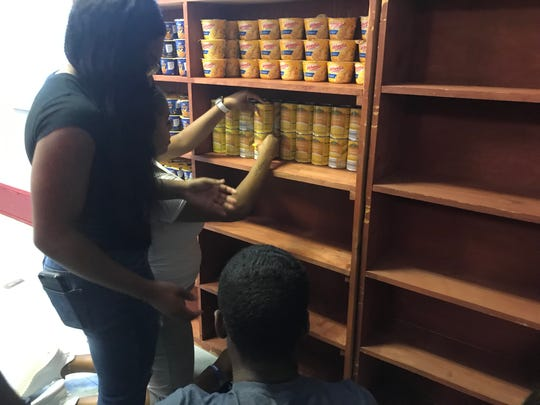 Students work to stock up the Lane College food pantry after RIFA donated 207 lbs. of nonperishable food items.