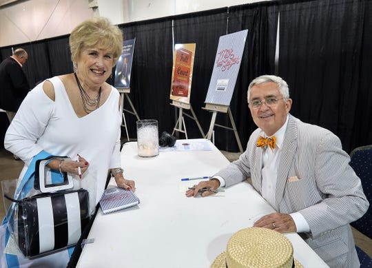 Haltom signs books after he spoke for the Jackson-Madison County Library on Monday.