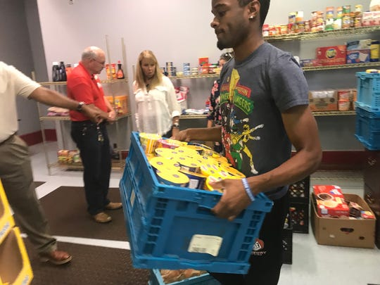 A student carries a box of donations from RIFA. The organization donated 207 lbs. of food items to Lane College's food pantry.