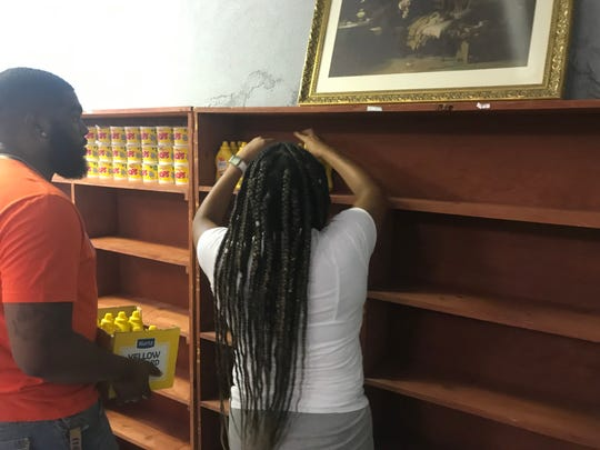 Niajah Walker and Patrick Batson, a Lane Colle senior and junior, respectively, stock the Lane College pantry with donations from RIFA on Tuesday.