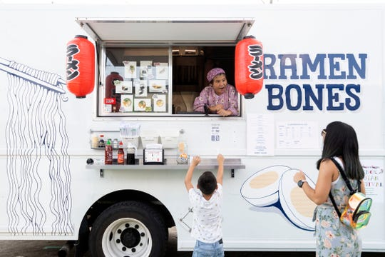 Kumi Alderman greets customers from the Ramen Bones food truck on Sunday, Aug. 18, 2019.